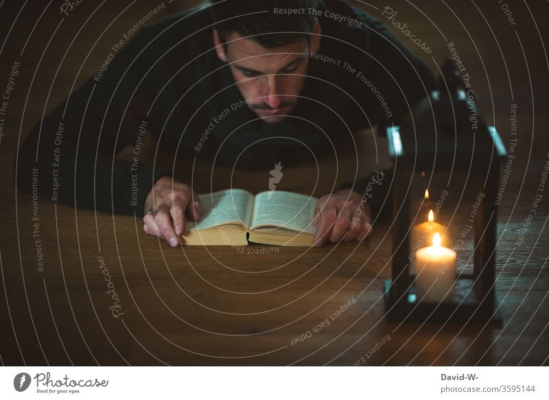 read an exciting book by candlelight Reading Book Candlelight shoulder stand Lantern Man Reader Ground Literature Education Academic studies Novel Tension