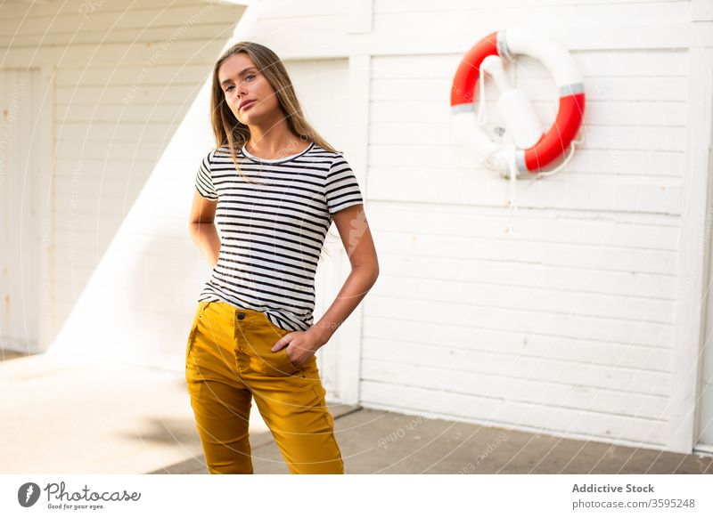 Stylish woman on quay near building with lifebuoy lifesaver style trendy stripe port calm female wall wooden stand young confident summer relax fashion content