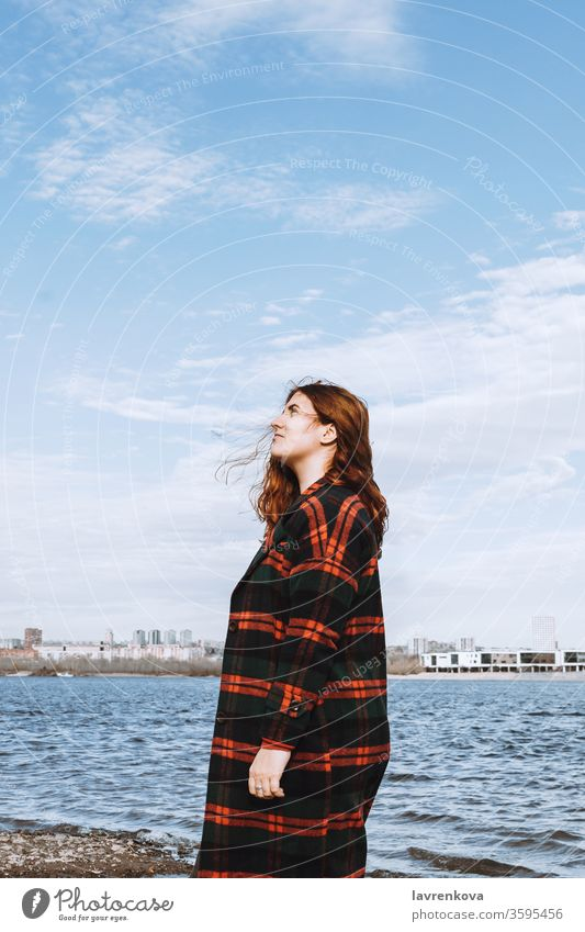 Lifestyle portrait of the young adult red-haired woman in checked coat on the bank of a river or sea, selective focus water bright white travel pretty beach