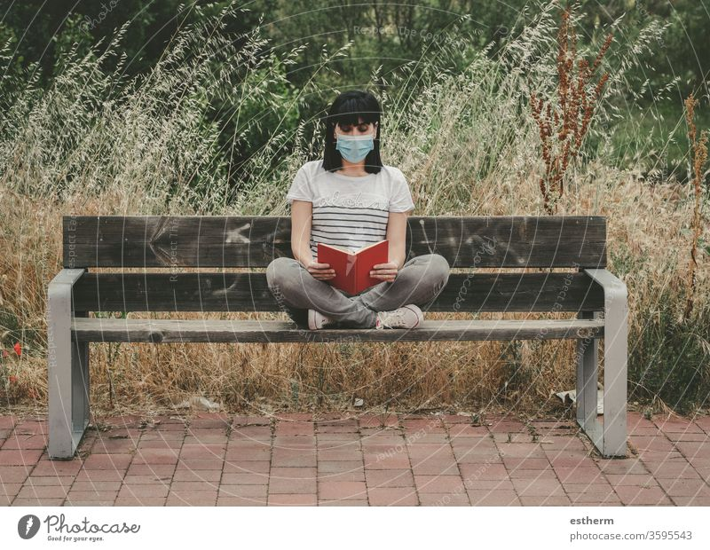 woman wearing medical mask reading a book sitting on a bench coronavirus young woman covid-19 virus dream relax epidemic pandemic quarantine leisure lifestyle