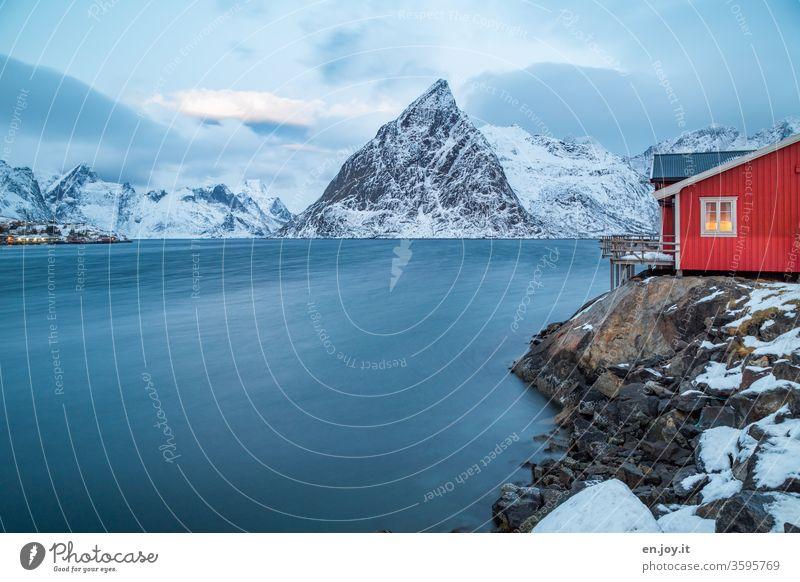 "red fishing cottage by the fjord in winter Lofoten,"" Olstinden Hamnøy Reinefjorden Fishermans hut Rorbuer Hamnöy stilt house Water Winter vacation"