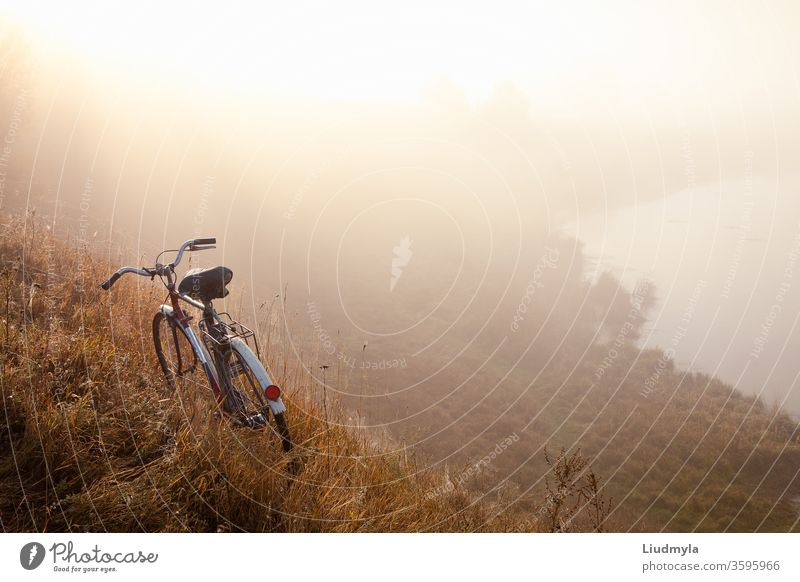 An old bicycle early in the morning in countryside and landscape mist.  Bicycle travel concept. Space for text male speed man active trail extreme action sport