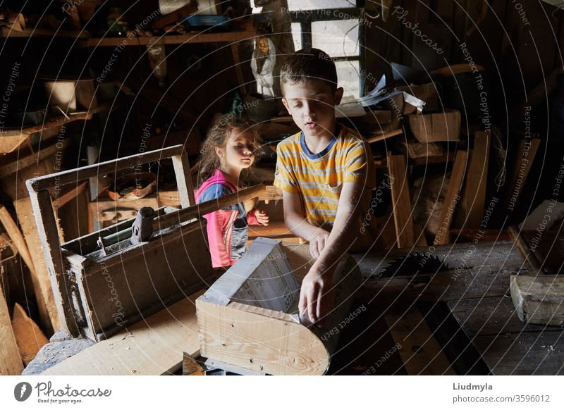 Young boy is making a wooden  bird house in the carpenter workshop. Curious little sister is trying to see what he is doing behind his back curious handyman