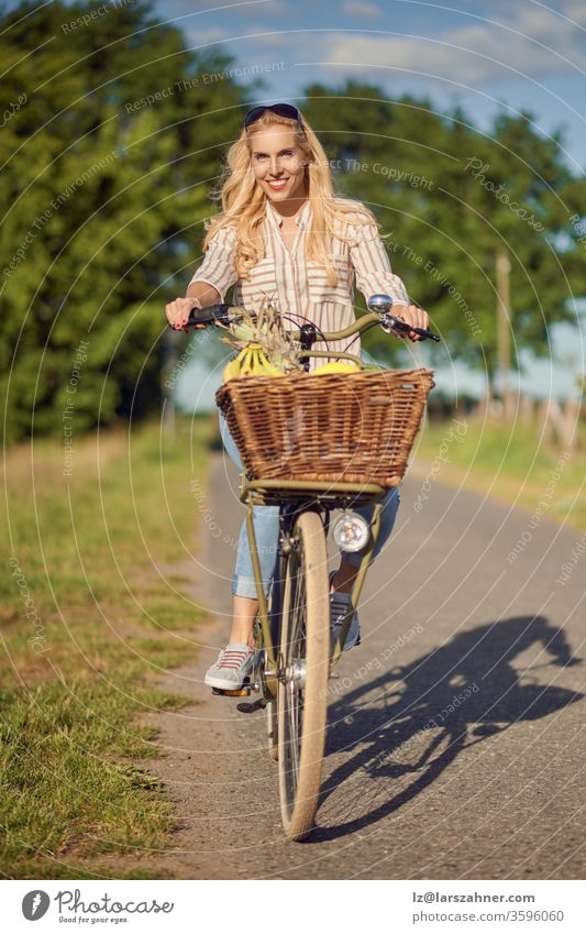 Happy woman smiling while riding a bicycle with a basket full of fresh and healthy fruits in a sunny day of summer in the countryside happy rural track meadows