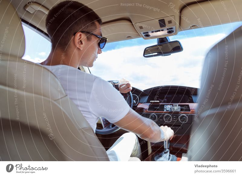 Young stylish man in sunglasses driving a car. View from the back, with the rear passenger seat. male vehicle automobile inside road day one wheel transport