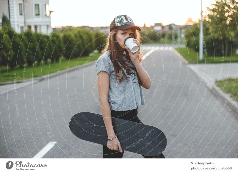 The girl with an active lifestyle starts with morning coffee and skating. Cup Coffee Drinking Woman Street Style Fashion youthful Easygoing already Outdoors
