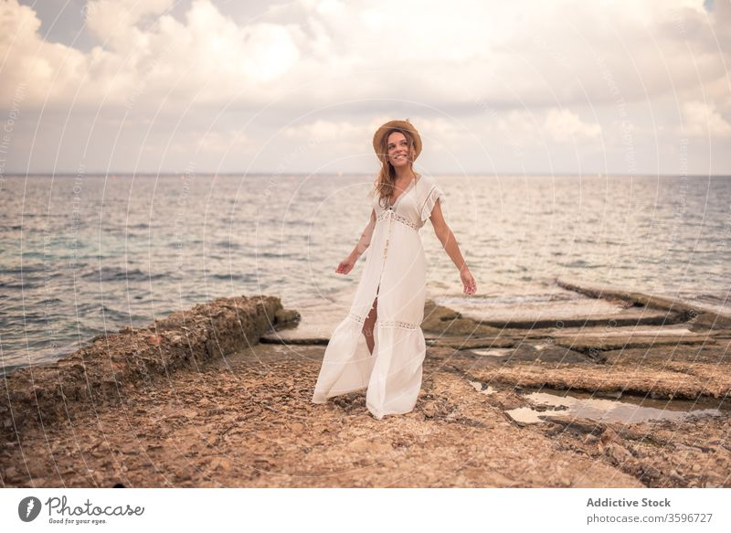 Content woman in dress and hat at seaside carefree travel seascape content smile summer holiday seashore female levanzo island stone traveler vacation beach