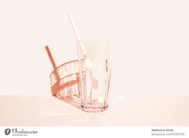Empty glass with straw in studio empty glassware crystal drink beverage refreshment transparent cold plastic summer serve creative simple minimal shadow shiny