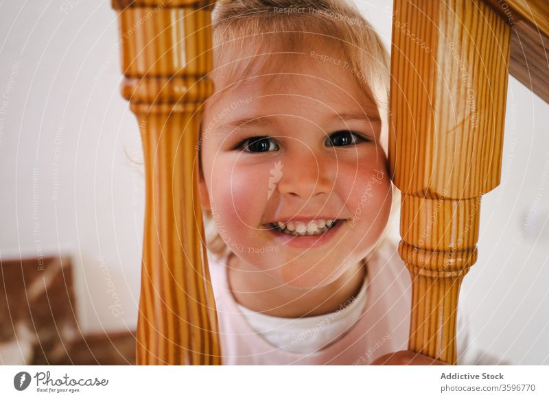 Playful girl with head in stairway railings funny home stuck cute leisure playful step interior wooden pretty cheerful house staircase child kid rest casual