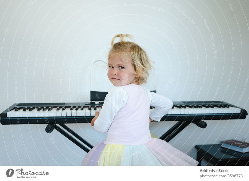 Cute girl learning to play modern piano home synthesizer study childhood cute music class skirt schoolgirl education practice prepare little adorable activity