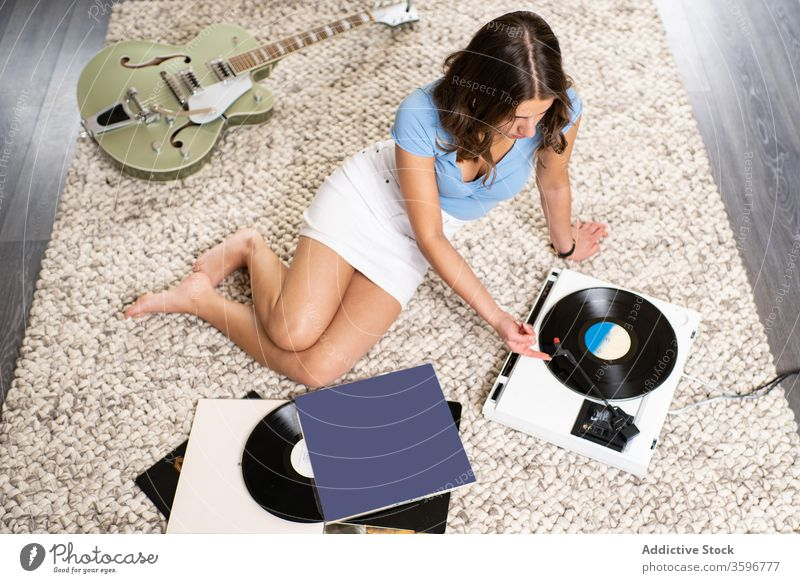 Young woman listening to music on vinyl disc record player home rest retro meloman young female sound melody song audio tune hobby device entertain lifestyle