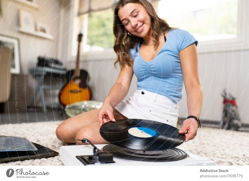 Young woman listening to music on vinyl disc record player smile home rest retro meloman young female sound melody song beautiful happy audio tune entertainment
