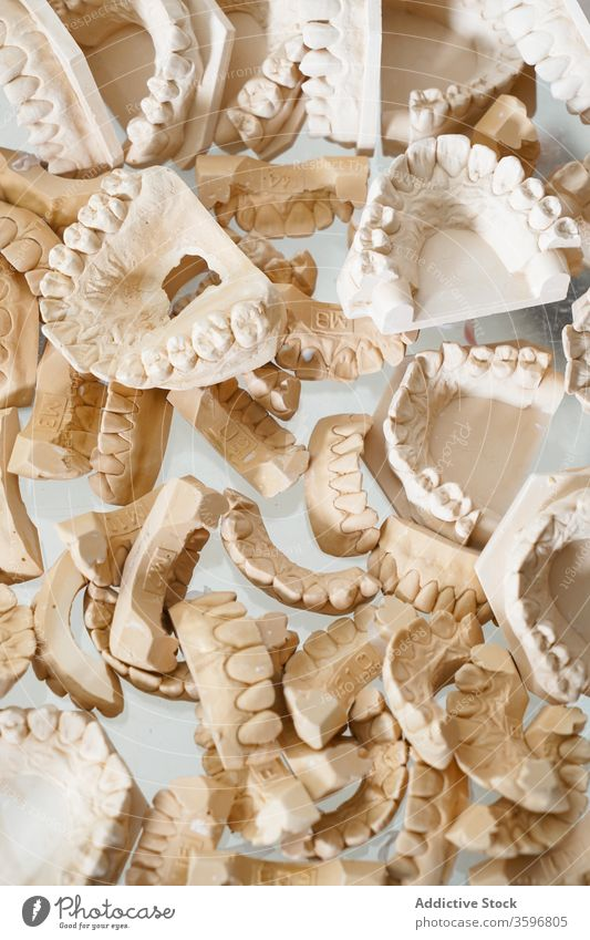 Set of dental casts in laboratory jaw model orthodontic artificial dentistry teeth set tooth plaster gypsum background abstract heap pile chaotic medicine