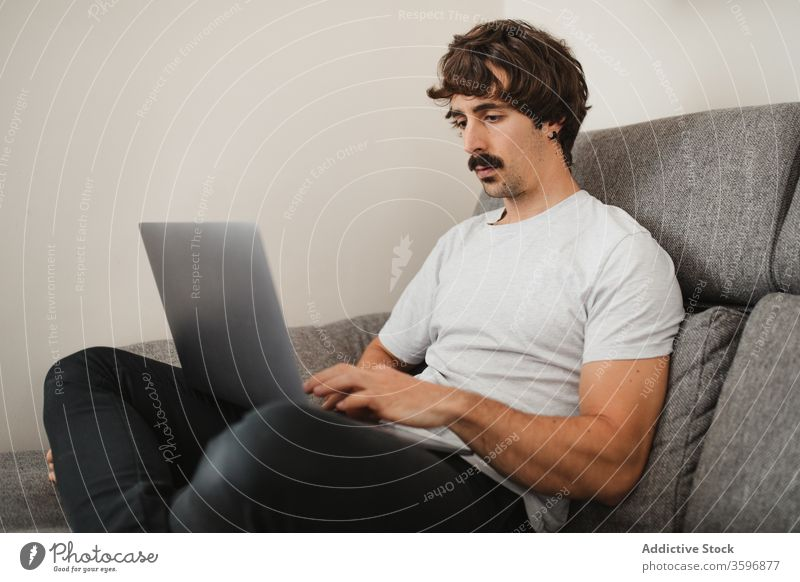Handsome male freelancer using laptop in living room entrepreneur remote project man work online concentrate home browsing internet device busy computer job