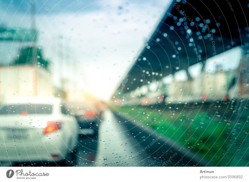 Rain drops on windshield. Car driving on asphalt road on rainy day. Windshield window of car with raindrops on glass windscreen. Traffic jam on rainy season. Bad weather in stormy day. Travel by car.