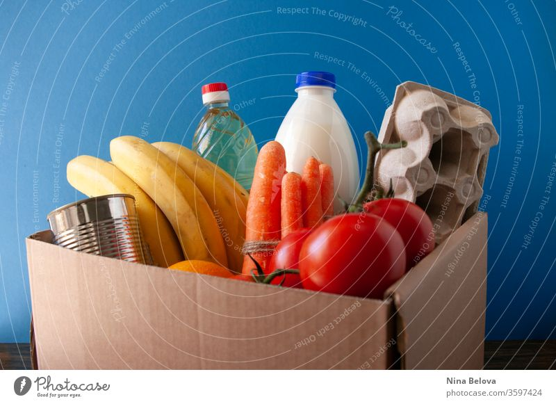 Food delivery.box with grocery. On blue background. tomatoes,bananas,milk,eggs,canned food,oil. Donation. donate service giving charity assistance social