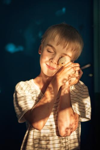 Little boy is tenderly holding and hugging a small chicken in his hands in sun rays. Loving animals concept face farmer favorite gentle tenderness feelings