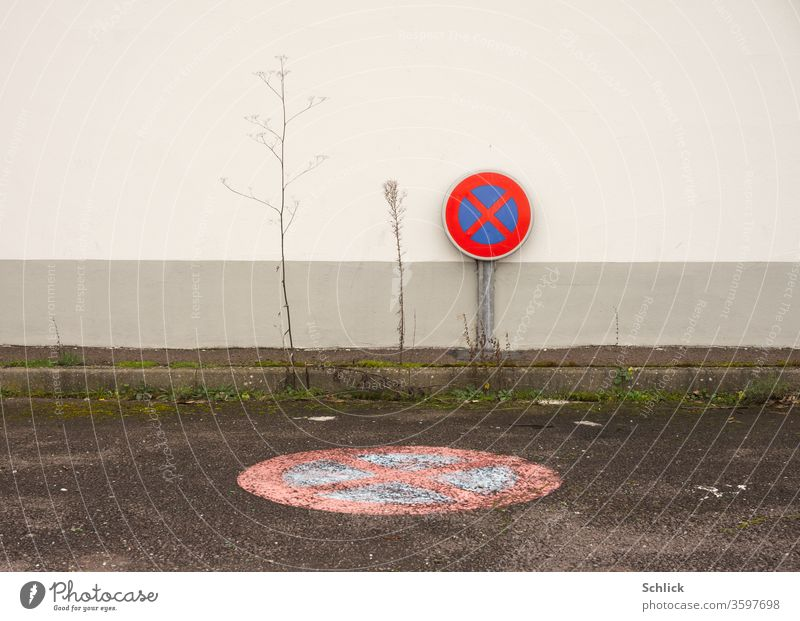 Useless no stopping sign in front of a wall with dead plants and no stopping as a symbol on asphalt No standing Places Asphalt Dry bankrupt Insolvency Parking