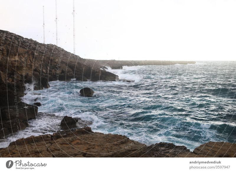Waves hitting the rocky cliffs in a beach located in Cyprus,This weather might be dangerous for water sports but simultaneously the waves and their splashes are pretty and wild