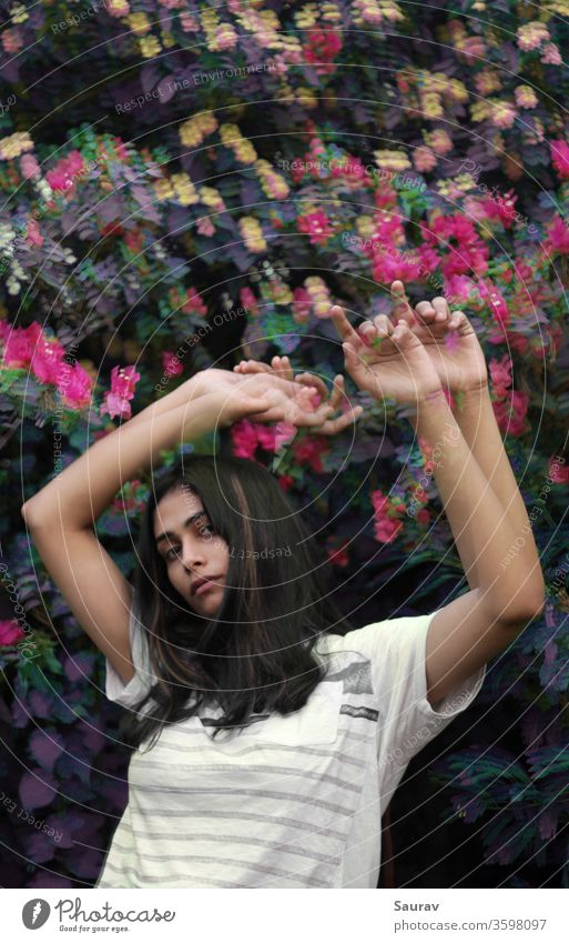 Young woman with medium length waving her hands raised up in front of colorful flower bush. Glitch effect. Youth (Young adults) Youth culture