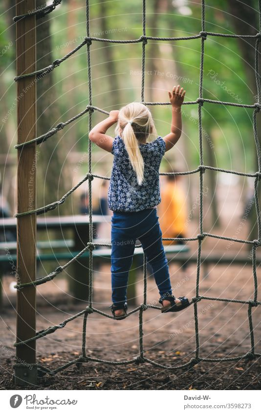 Playground - girl climbing up a climbing net climbs Joy fun Euphoria Tall courageous Brave To hold on detaining Responsibility dare high up upstairs Above