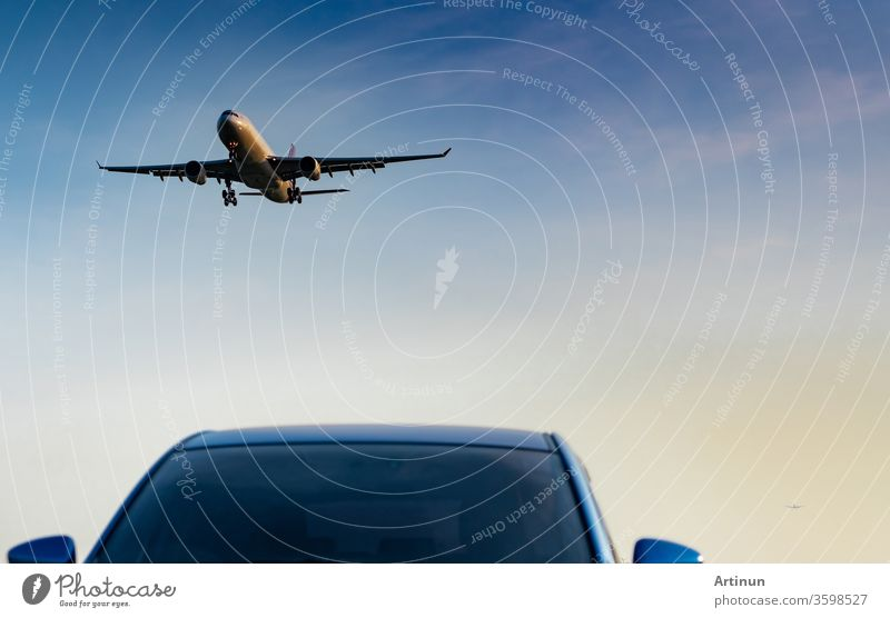 Commercial airline. Passenger plane landing approach blue SUV car at airport with blue sky and clouds at sunset. Arrival flight. Vacation time. Happy trip. Airplane flying on bright sky. Car parked.