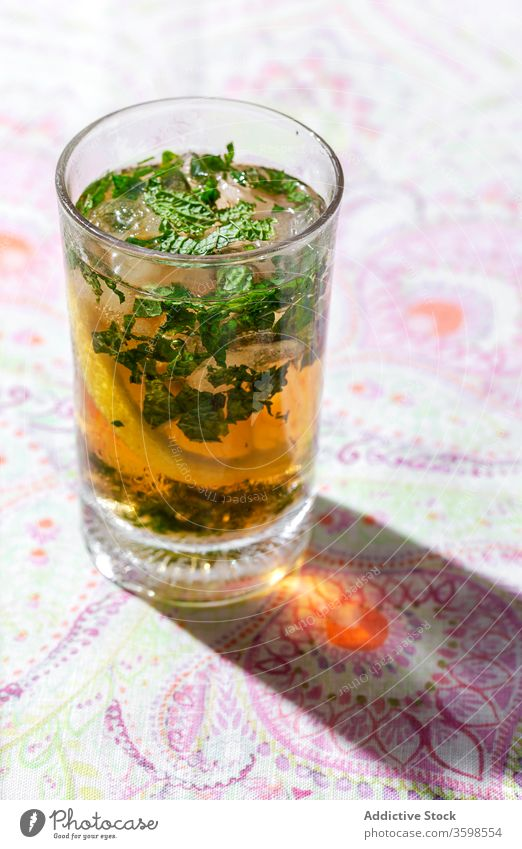 Iced tea with lemon and mint in glasses on table cold ice drink cafe refreshment citrus beverage cool fruit slice liquid cube delicious tasty healthy ingredient