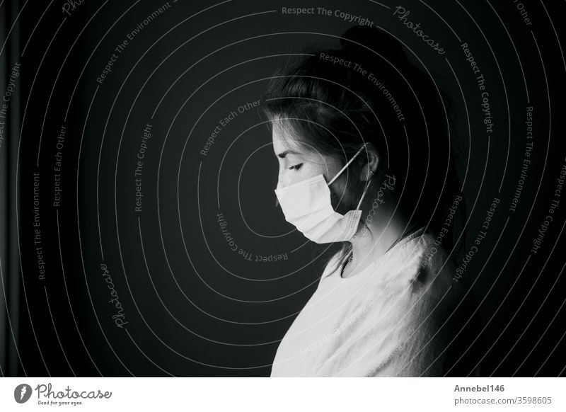 Young woman wearing protection mask against Covid-19, Coronavirus looking depressed and isolated, black and white portrait virus concept background medical