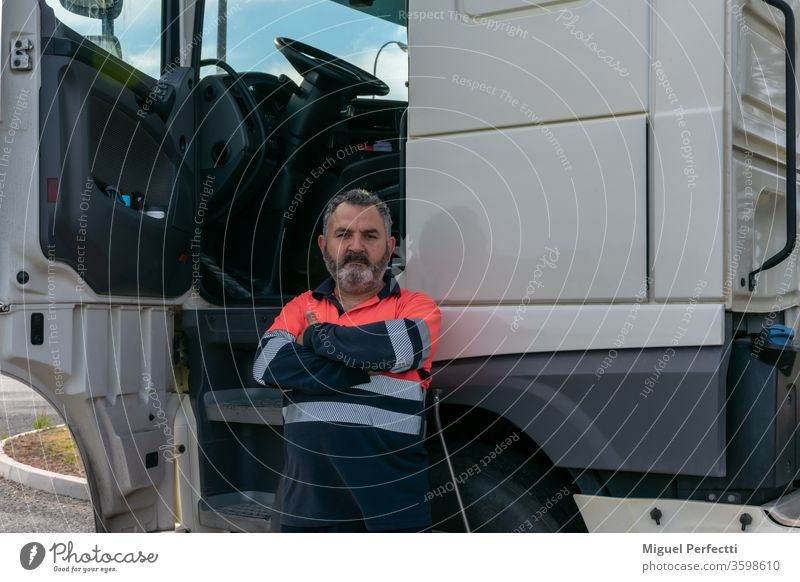 Truck driver posing next to the truck cab with the door open truck driver man trucker experiencie professional veteran high visibility cabin transport