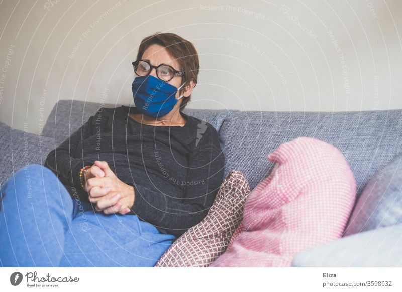 A woman sits on the sofa at home with a mask to protect her from being infected with Corona. Mask Woman Sofa Face mask portrait Sit corona Virus Protection