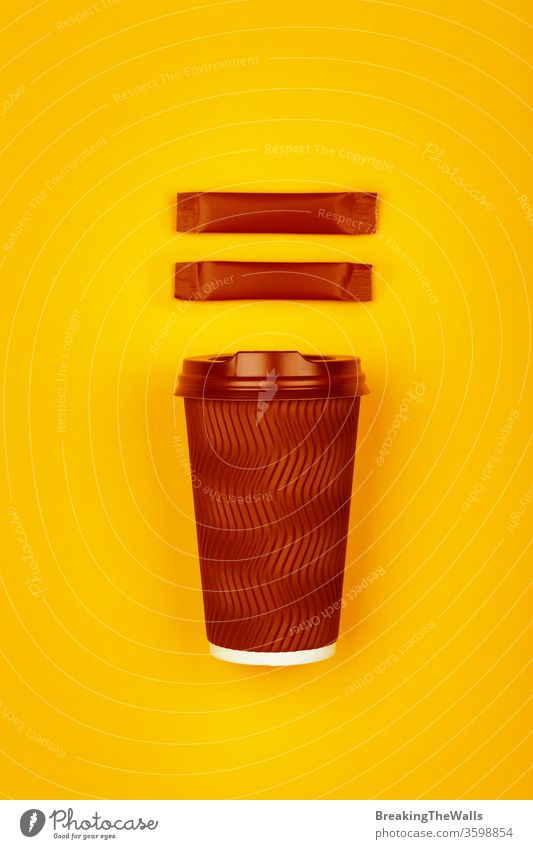 Brown paper coffee cup over yellow Coffee tea disposable brown dark one cap vivid stick sachet two sugar background closeup hot drink beverage takeaway copy