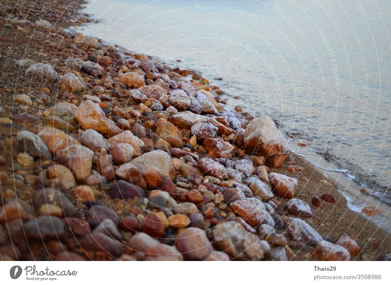 sunset at the dead sea beach shore coastline pebbles stones ocean nature landscape evening beautiful beauty natural sunny nobody water dark rock material group