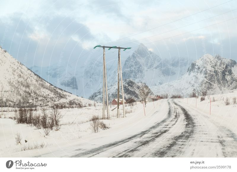 snowy road in Norway leads under a power line in front of mountains with snow Lofotes Scandinavia Winter Snow Street Electricity pylon power supply Climate