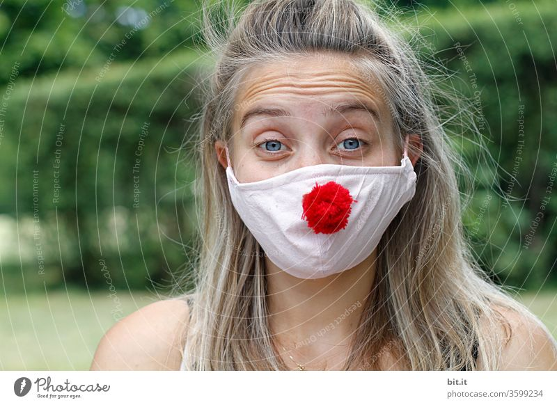 Young pretty woman looks anxiously into the camera with wrinkled forehead and mask. Red Nose Day with funny, funny clown mask, with red bobble, pompom to protect against corona. Blonde, young, long-haired woman with cool face mask outside in the nature.