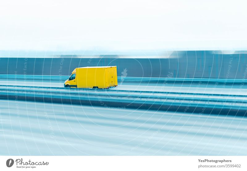 Delivery truck on the highway. Yellow van in motion asphalt automobile blank business car cargo copy space courier delivery driving empty fast freeway freight