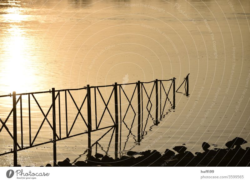 A railing leads in a river in which the evening sunlight is reflected Metal Line Back-light Construction Water River River bank sunlight rays Sunlight