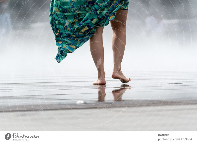the young woman walks barefoot over a wet surface - the spray of the Miroir d'eau provides a welcome cool-down Barefoot feet Legs leg Wet Toes Skin Water Shadow