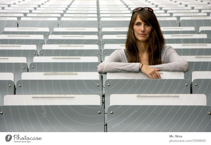 young woman sitting in the second row spectator seats Audience Event Seating Places Empty tribune Row Row of seats Side by side Structures and shapes boardroom