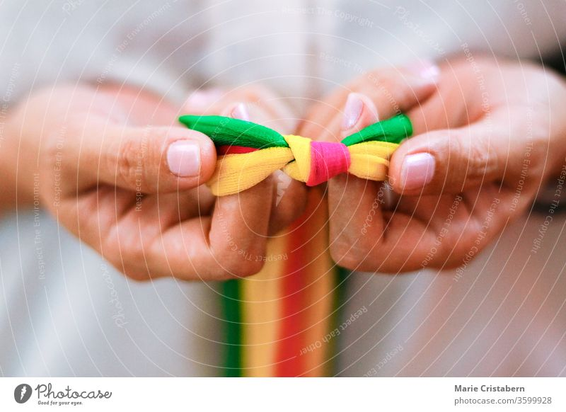 Hands holding rainbow colored ribbons in celebration of Pride Day, diveristy, equality and the LGBTQ community pride day Pride concept Pride colors lgbtq+