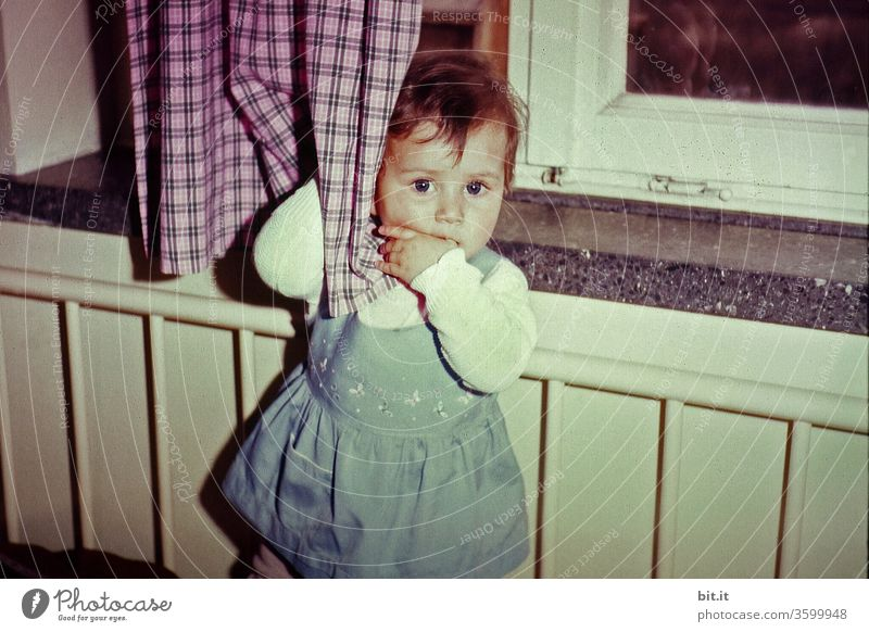 alt l thoughtful, shy, shy toddler, plays with plaid curtain in playpen Sensitive girl in the sixties in old building flat stands at the window and sucks her thumb. Lost, sad war grandchild in 60s retro style.