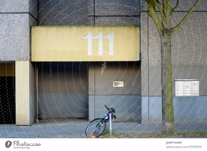 House number 111, number of angels Facade Entrance Architecture Prefab construction ring Mailbox Gloomy Weathered Ravages of time Subdued colour Bicycle