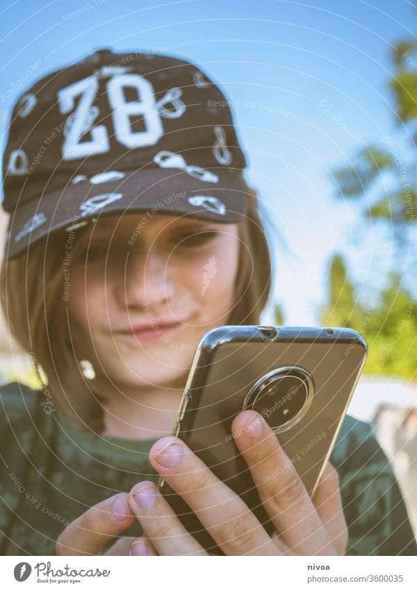 boy with smartphone Boy (child) Cap childhood Camera Summer Child Infancy Looking into the camera Childhood memory Human being Portrait photograph Colour photo