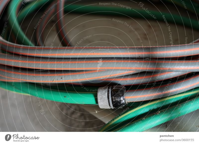 Garden hoses rolled up. Gardening Water hose Flake stripe pattern Cast Hose Shadow green Gardener