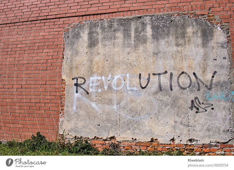 Graffiti lettering REVOLUTION on wall plaster on a red brick wall Revolution lettering Characters Wall (barrier) Facade built Wall (building) Copy Space left