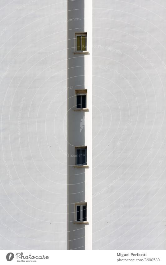 Detail of a building, where only a row of small windows is seen vertically facade apartment architecture tower skyscraper urbanization construction glass white