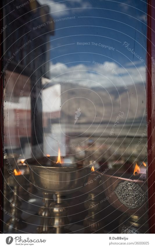 Ancient Tibetan oil lamps behind a window pane reflecting a mountain range of the Himalayas. Rock Nature mountains Valley Tall Colour photo Sky Clouds Landscape