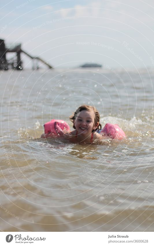 Infant with a waterwing bathing in the North Sea bathe chill Fresh Swimming & Bathing Drop Drops of water Water Ocean Footbridge girl Comical muck about Waves