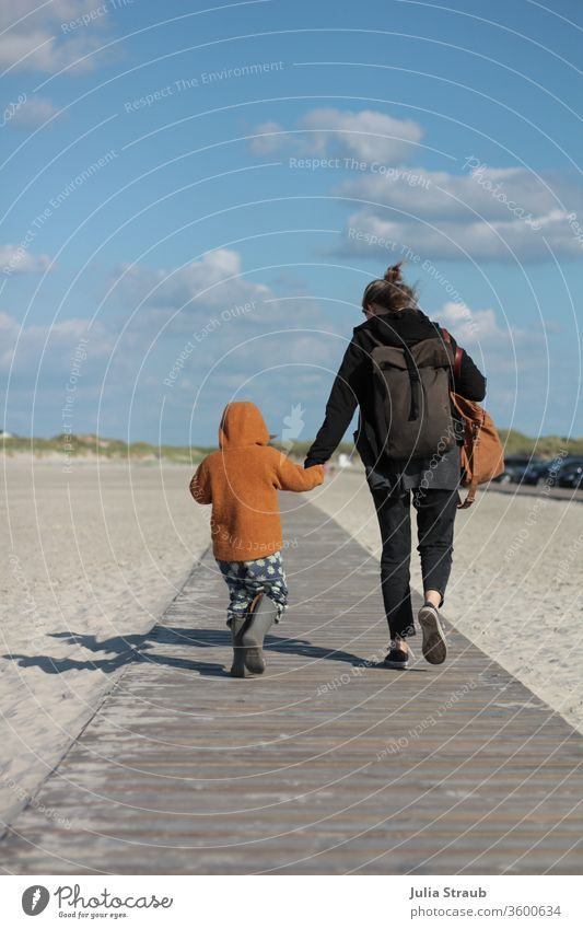Woman and child walking holding hands on a wooden path to the beach Sand white sand North Sea dunes Marram grass Backpack backpacker Toddler wollwalk