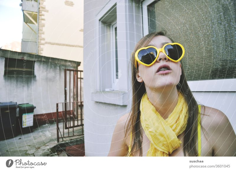 teenager with yellow heart sunglasses and yellow scarf in yellow bikini stands in a somewhat run-down backyard and looks up girl Young woman