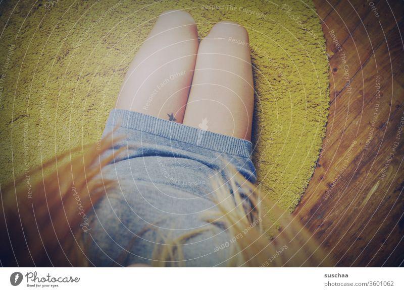 sitting on the floor looking at your own legs | symmetry Woman feminine Legs Feminine Carpet sedentary hair wooden floor Tattoo Stars Symmetry Interior shot